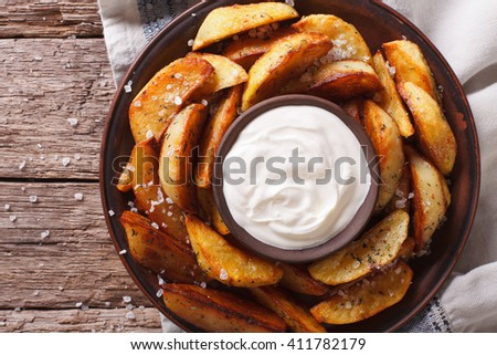 Spicy potato wedges with herbs and mayonnaise on a plate closeup. Horizontal view from above