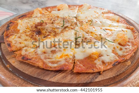 Spicy prawn pizza (Tom Yam Kung) on wood plate - stock photo