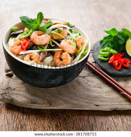 spicy prawn vietnamese rice noodle chili mint basil spring onions stir fry broth pho - stock photo