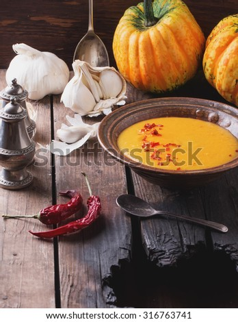 Spicy pumpkin cream soup served in the vintage ceramic bowl with cream and chili flakes on rustic wooden background