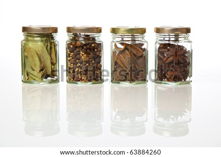 Spicy range. A range of four transparent glass jars of different spices and herbs. - stock photo