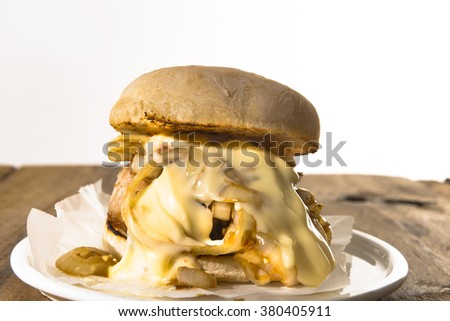 Spicy roasted pork bun with chili sauce and onion on wood table. White background - stock photo