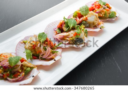 Spicy salad with deep-sea scallops in Thai style on black background - stock photo