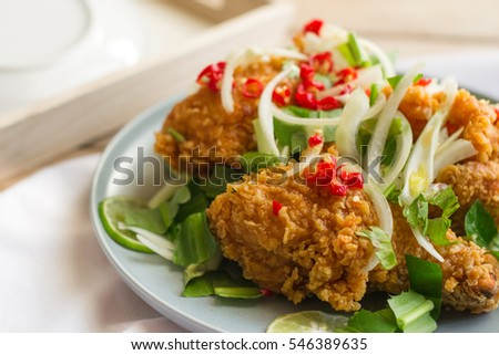 Spicy salad with fried chicken in grey dish on wooden table.