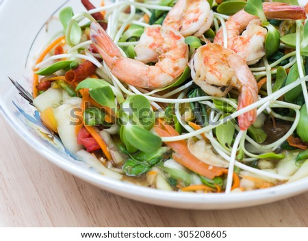 Spicy salad young green sunflowers seedling with shrimps - asia food Close up