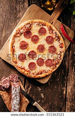 Spicy salami or pepperoni pizza with a red hot cayenne chili being prepared in a rustic kitchen on an old wooden counter, overhead view - stock photo