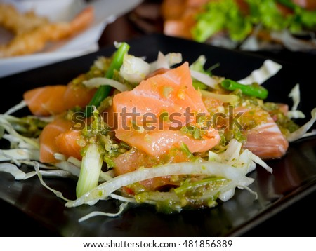 Spicy salmon salad on wood table