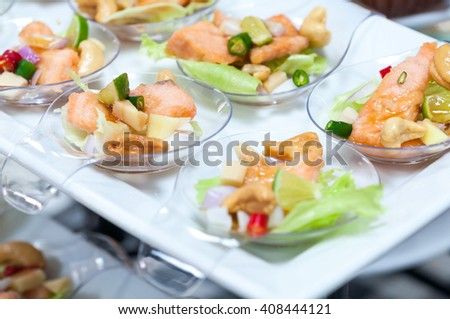 spicy salmon salad snacks on plastic spoons, selective focus