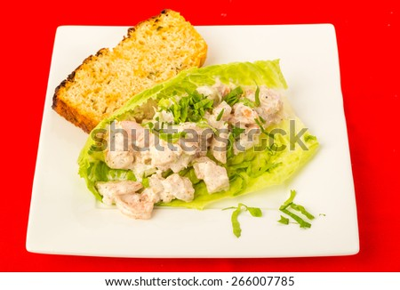 Spicy seasoning on shrimp salad in lettuce leaf wrap with slice of jalapeno cheese loaf on bright red tablecloth background. - stock photo