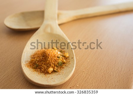Spicy seasoning powder on wooden spoon, selective focus - stock photo