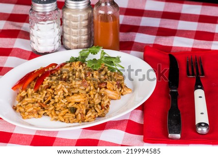 Spicy Shrimp and Chicken Jambalaya in typical Cajun Restaurant Setting.  Red Plaid Tablecloth and red cloth napkin. - stock photo