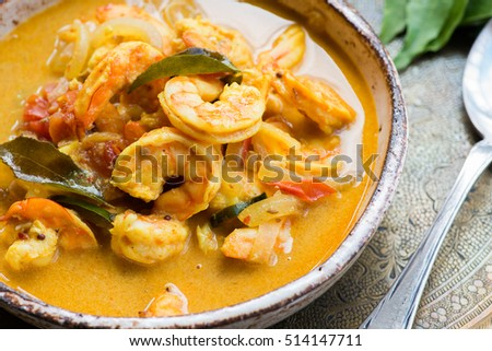 Spicy shrimp curry with coconut milk and chili in bowl, selective focus, closeup. Indian food, conju curry.