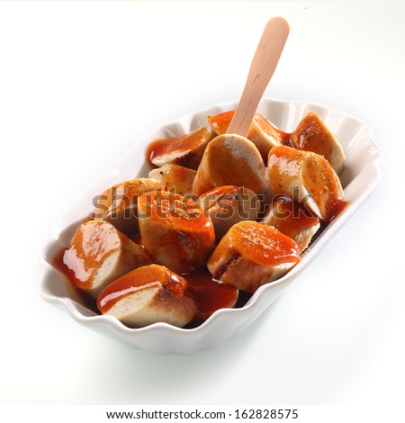 Spicy smoked sausage with ketchup served sliced in a decorative fluted white bowl with a small wooden fork - stock photo