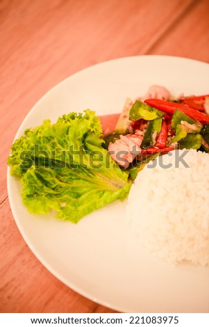 Spicy stir fried salmon and white cooked rice dish  - stock photo