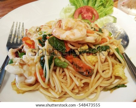 spicy stir fried spaghetti with seafood and basil leaves on white dish with spoon and fork, Thai fusion food with spaghetti on wooden table