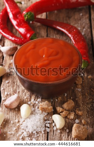 Spicy Thai chilli Sriracha sauce with ingredients close-up on the table. vertical