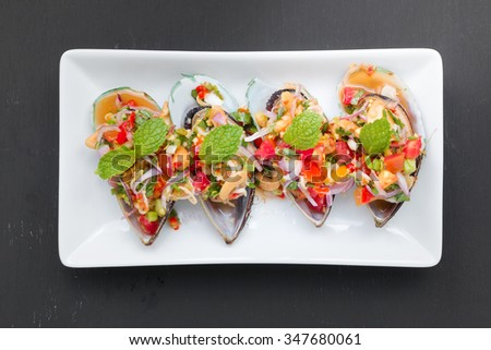 Spicy Thai style Mussel Salad on black background - stock photo