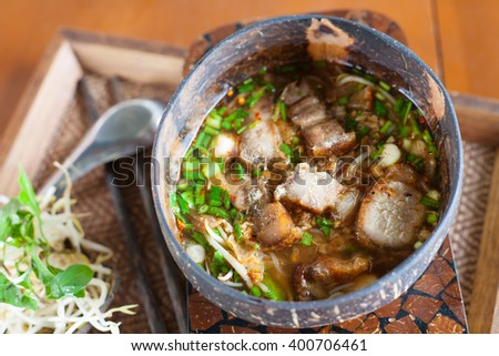 Spicy TOM YAM noodle soup with crispy pork and variety of vegetable in wooden bowl - stock photo