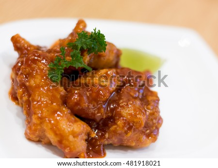 spicy tomato chicken with lemon on wood background