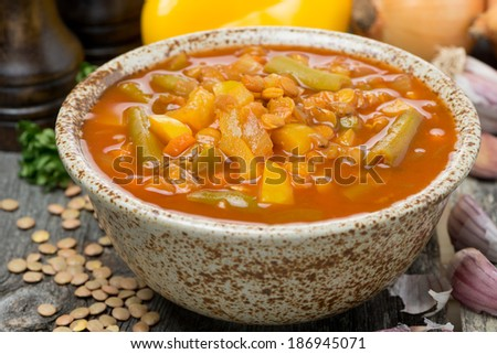 Spicy tomato soup with lentils and vegetables in a bowl, close-up - stock photo