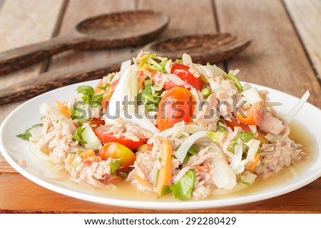Spicy Tuna Salad onion and tomatoes in plate put on wooden background , Thailand cuisine. - stock photo