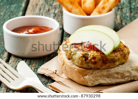 Spicy turkey burger on a wooden background - stock photo