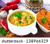 Spicy vegetable soup with red lentils, chili pepper and zucchini in a white ceramic bowl for dinner - stock photo