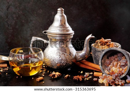 Spicy winter tea in a silver teapot and cup surrounded by aromatic ingredients including stick cinnamon, star anise, and caramelized sugar crystals - stock photo