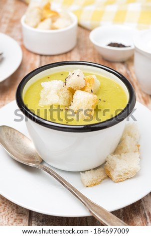 spicy zucchini soup with croutons in a cup, close-up, vertical - stock photo