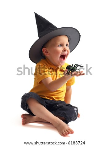 Spider hunting. Isolated image of black spider and small cute boy in witch hat - stock photo