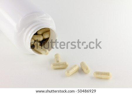 Spilled capsules from white prescription container - stock photo