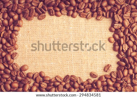 Spilled coffee beans frame over burlap textile - stock photo