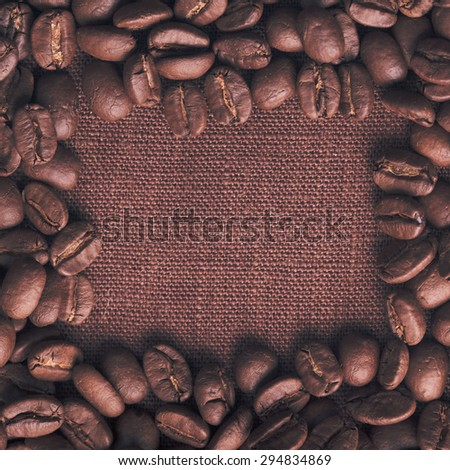 Spilled coffee beans frame over linen textile - stock photo