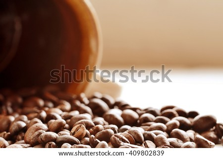 Spilled coffee beans from brown ceramic mug on white wood planks - stock photo