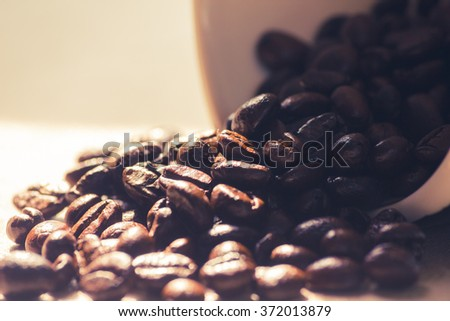 Spilled coffee beans from the white ceramic cup in vintage tone. - stock photo