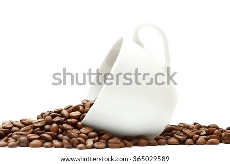 Spilled coffee beans from the white ceramic cup isolated on white background - stock photo