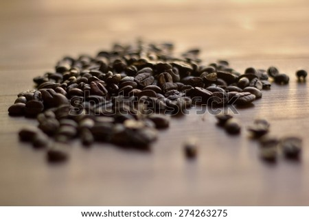 spilled coffee beans on the table in detail (Shallow DOF). - stock photo