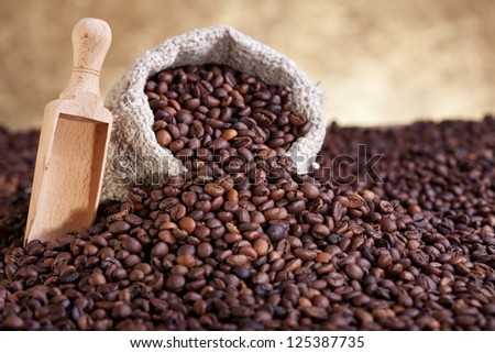 Spilled coffee sack and lots of roasted beans - stock photo