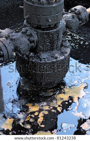 Spilled crude oil around oil field. Oil and Gas Industry. Environmental pollution.  - stock photo