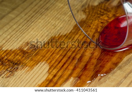 Spilled glass of wine on a wooden surface - stock photo
