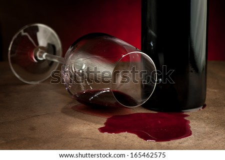 Spilled glass of wine on table after party - stock photo