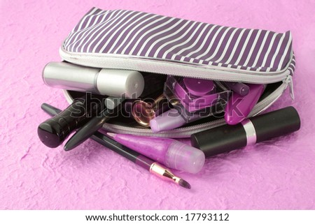spilled makeup from case on pink background - stock photo