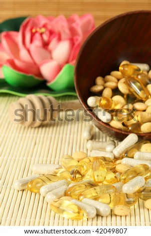 spilled natural vitamins supplements with wooden honey spoon and lotus in the background - stock photo