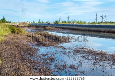 Spilled oil around the oil pipeline - stock photo