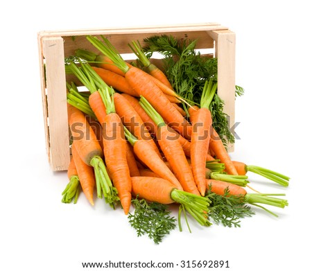 Spilled out carrot roots (Daucus carota ssp. sativus) from wooden crate on white