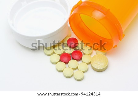 Spilled pill bottle and pills, high key . - stock photo