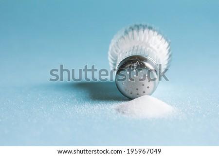 Spilled salt and saltshaker on blue background - stock photo