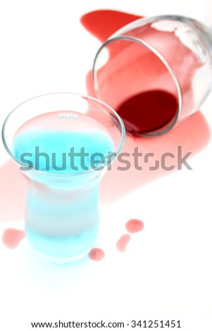 Spilled wine and a shot glass on a white background - stock photo