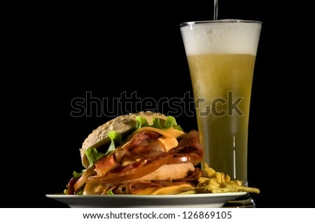 Spilling Glass of Beer and Big Tasty Burger with Fried Bacon, Lettuce, Tomato, Cheese and French Fries isolated on black background - stock photo