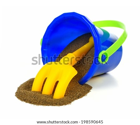 Spilling toy sand pail with rake over a white background - stock photo